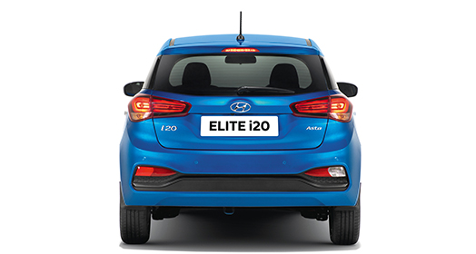 Side view of red Elite i20 driving out from the car garage