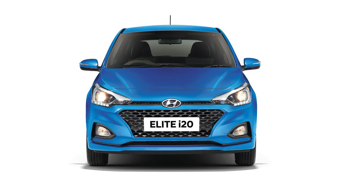 Side view of red Elite i20 driving fast on the road in the city